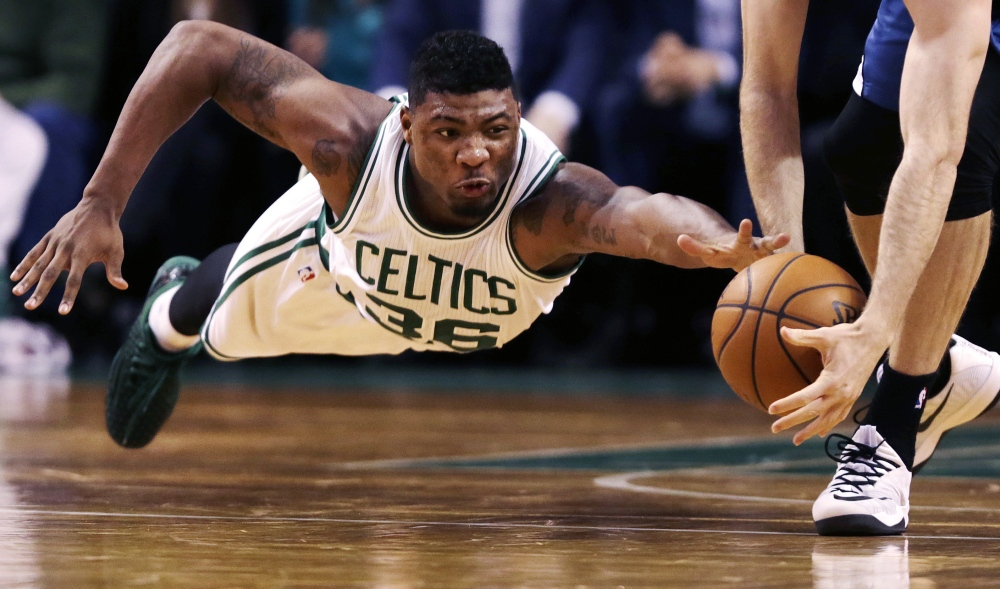 Celtics guard Marcus Smart goes to the floor as Minnesota Timberwolves forward Robbie Hummel picks up the loose ball during the second half of Friday night's 114-98 win by the Celtics.