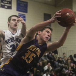 Andrew Roberts of Cheverus grabs an offensive rebound as Deering forward Jacob Coon tries to defend Friday in an SMAA boys' basketball game at Deering High. Cheverus fell behind 11-0 in the first quarter but eventually rallied to beat the previously undefeated Rams, 45-34.