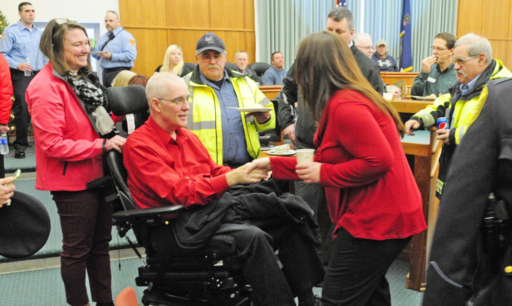 Augusta Police Chief Bob Gregoire, 49, is the center of attention at the city employee holiday luncheon on Friday at City Center in Augusta. His wife, Cathy Gregoire stands, behind his motorized wheelchair.