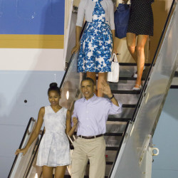 President Barack Obama, right, with his daughter Sasha, bottom left, the first lady Michelle Obama, top left center, and their other daughter Malia top right, disembark Air Force One  after arriving at Joint Base Pearl Harbor-Hickam for their annual family Christmas vacation Friday, Dec. 19,, in Honolulu. The first family will be staying in Kailua, Hawaii.