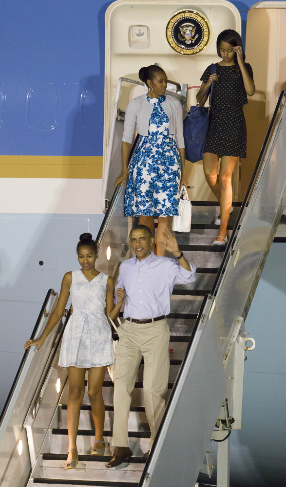 The Obamas disembark Air Force One after arriving at Joint Base Pearl Harbor-Hickam for their annual Christmas vacation Friday in Honolulu. The first family will be staying in Kailua.