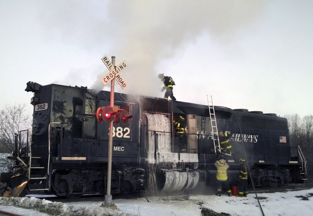 Monmouth firefighters work to extinguish a locomotive fire on a Pan Am Railways train Saturday morning near Berry Road in Monmouth.