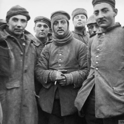 In this image provided by the Imperial War Museum, World War I German and British soldiers stand together on the battlefield near Ploegsteert, Belgium during Dec. 1914. Soldiers who had been killing each other by the tens of thousands for months climbed out of their soggy trenches to seek a shred of humanity amid the horrors of World War I. Hands reached out across the divide and in Flanders Fields a century ago, a spontaneous Christmas truce ever