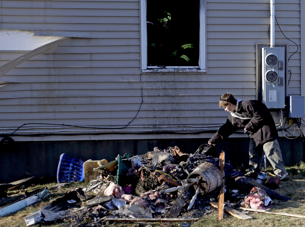 Greg Ballou, 26, of Freeport, looks through the rubble of a fire that destroyed his home on Varney Road on Saturday. Ballou and his wife, Ardelle, lost a cat and a dog in the blaze.