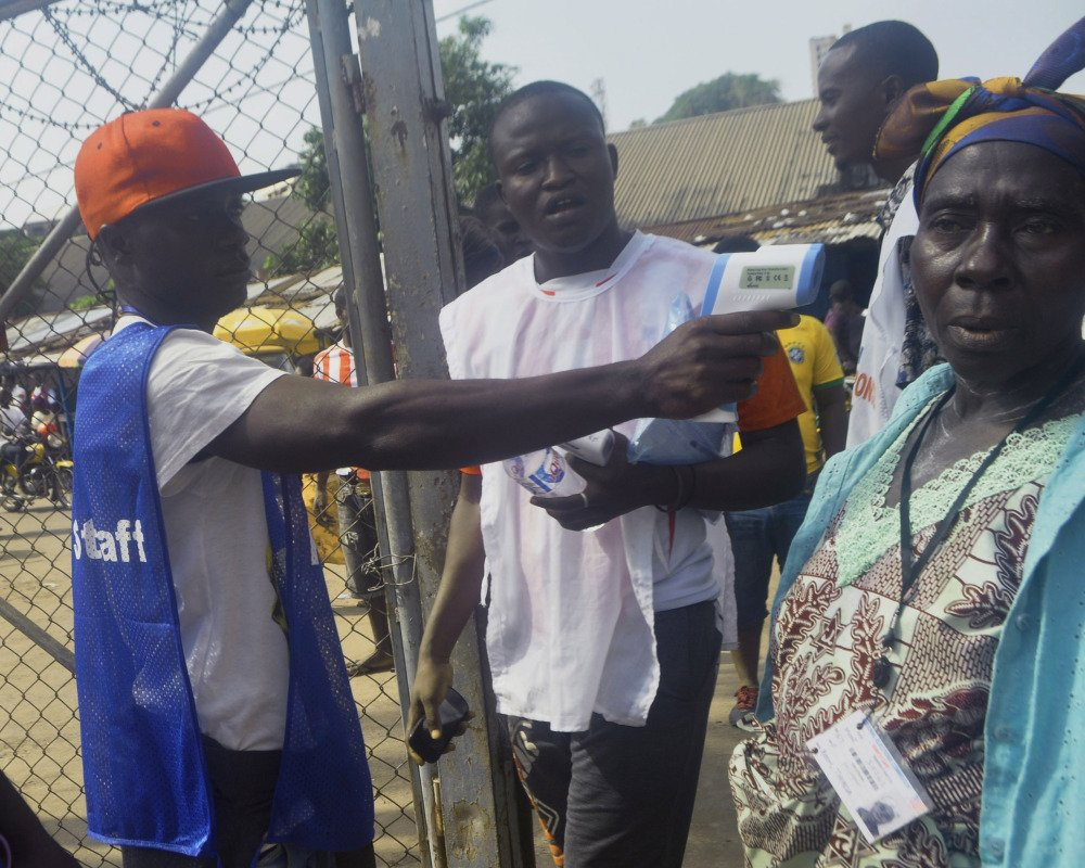 An election worker takes the temperature of a voter in the West Point slum before she casts her vote Saturday during a Liberian election.