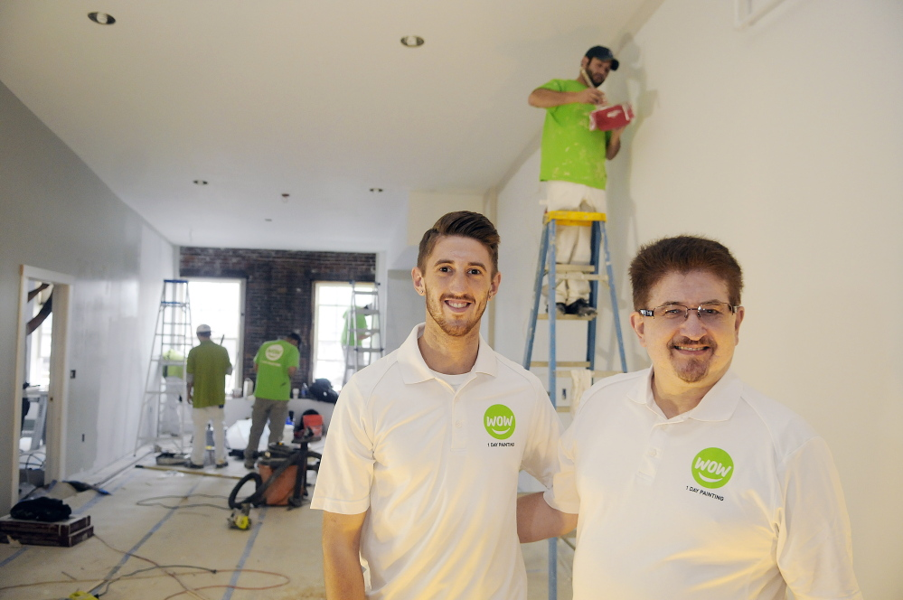 Ryan Guerrette and his father, William, at the Augusta apartment building their family owns on Thursday. The men have opened a Wow 1 Day Painting franchise.