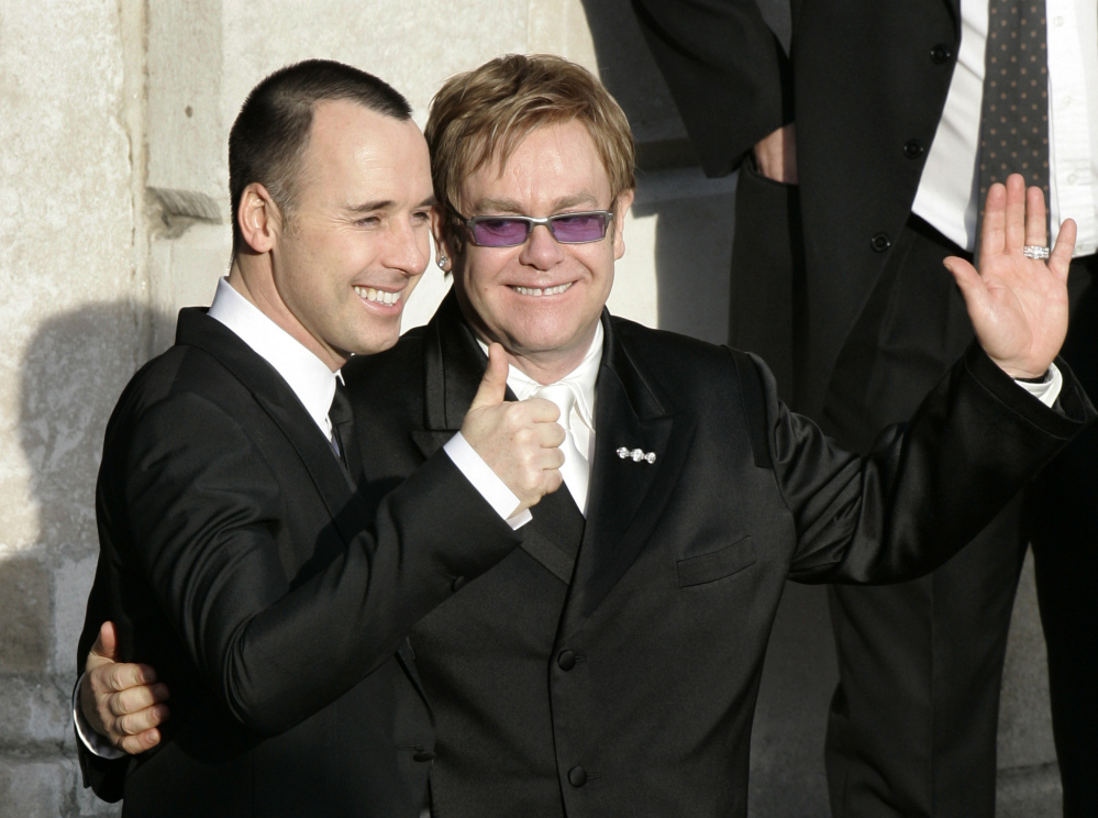A December 2005 photo shows pop star Elton John, right, and his longtime partner David Furnish, embracing as they wave to members of the media and the public after they had a civil ceremony at the Guildhall in Windsor, England. John and Furnish officially married on Sunday.