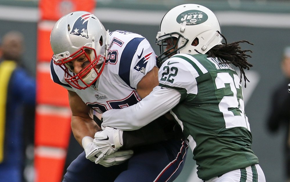 Marcus Williams of the Jets tackles New England's Rob Gronkowski during the second half Sunday at East Rutherford, N.J.
