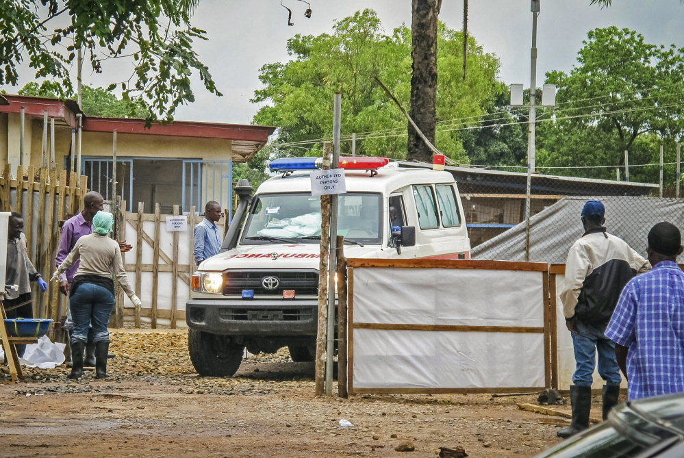 An ambulance leaves an Ebola isolation unit at the Kenema Government Hospital in Kenema, Sierra Leone, carrying the highly contagious bodies of the dead to a burial site.