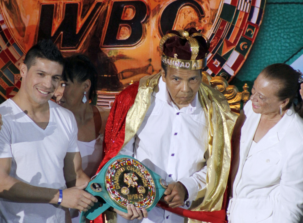 "Former heavyweight boxing champion Muhammad Ali is crowned ""King of Boxing"" while accompanied by his wife, Lonnie, right, and Argentine boxer Sergio Martinez during the 50th convention of the World Boxing Council in Cancun, Mexico."