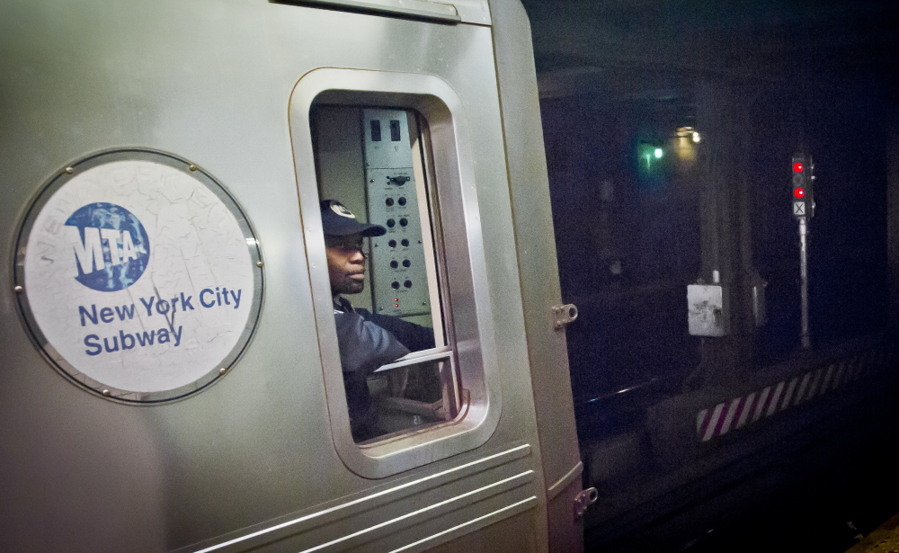 A Metropolitan Transit Authority subway train operator in New York waits for red-light signal to turn green. The signal is controlled by a manual subway interlocking switch and signal system that is eight decades old.