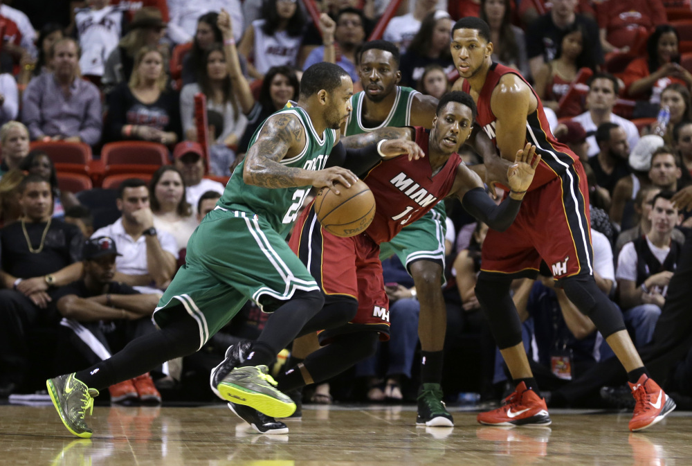 Boston guard Jameer Nelson drives against Miami's guard Mario Chalmers (15) on Sunday in Miami. Nelson played his first game with the Celtics, who lost to the Heat 100-84.