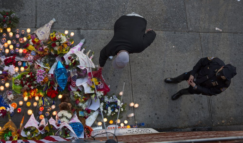A man leaves flowers Sunday at a growing memorial for two New York City patrolmen who were shot in their car Saturday. The gunman then went into a nearby subway station and killed himself, police said.