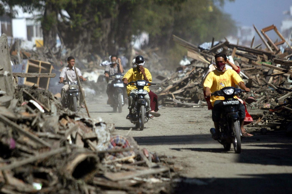 Motorists ride through debris in Banda Aceh, Indonesia, in December 2004 after a gigantic wave hit. The city is now almost totally restored.