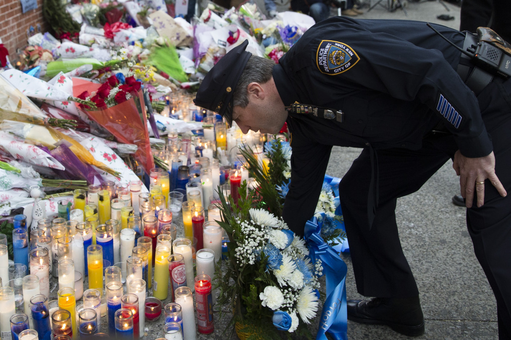 Patrick Lynch, president of the Patrolman's Benevolent Association, places flowers at a makeshift memorial on Monday near the site in Brooklyn where New York police officers Rafael Ramos and Wenjian Liu were killed Saturday. Police say Ismaaiyl Brinsley ambushed the officers in their patrol car in broad daylight before killing himself in a subway station.