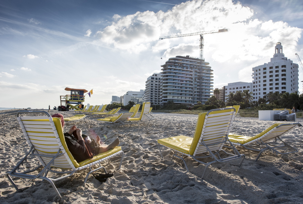 A day at the beach may include the hustle and bustle of construction as developers create and cash in for a demand of high-end Miami Beach properties – some of which foreigners buy as investments and never set foot in.