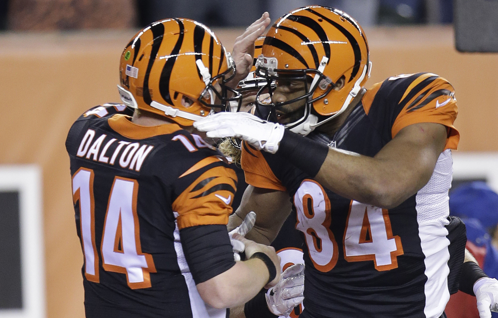 Cincinnati Bengals tight end Jermaine Gresham (84) is congratulated by quarterback Andy Dalton after Gresham made a 2-yard touchdown reception during the first half of Monday night's game against the Denver Broncos. The Bengals won to clinch a playoff berth.