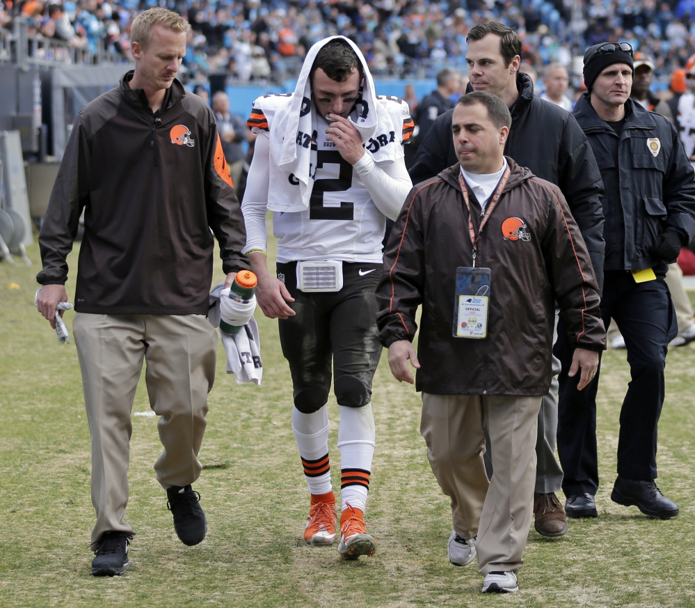 The Cleveland Browns' Johnny Manziel is helped off the field after being injured in the first half of Sunday's game against the Carolina Panthers. Manziel's rookie season in the NFL wasn't what he or the Browns or his legion of fans expected. He started one game, couldn't make it through his second without getting hurt, and didn't look like a franchise-changing quarterback.