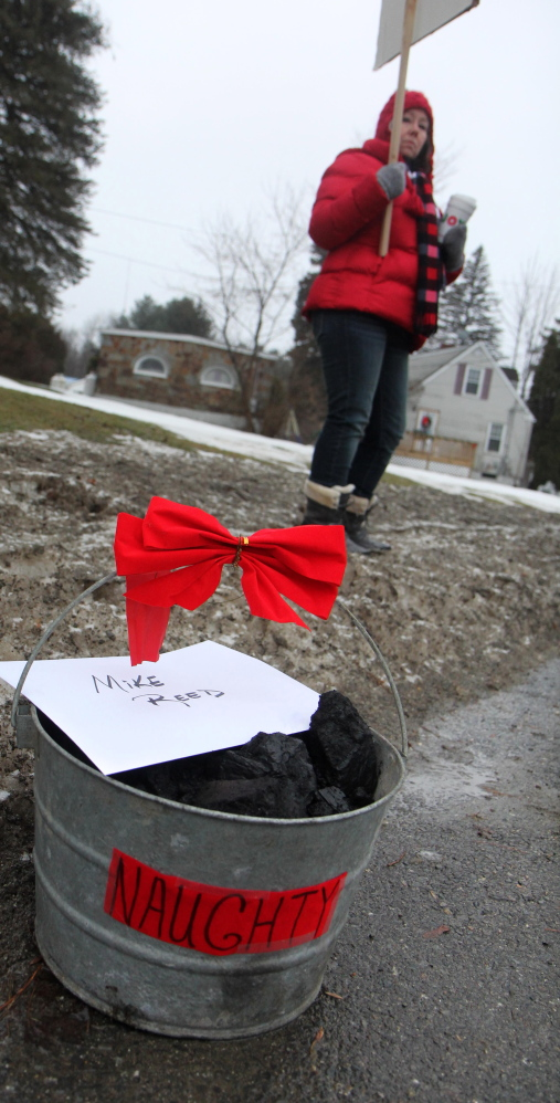 """Strikers put a bucket of coal and a """"note from Santa"""" on the sidewalk near the home of FairPoint's Maine president."""