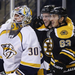 Boston Bruins left wing Brad Marchand (63) celebrates his goal with teammate Reilly Smith as Predators goalie Carter Hutton looks on during the second period of Tuesday night's game in Boston. Marchand scored two goals in the game.