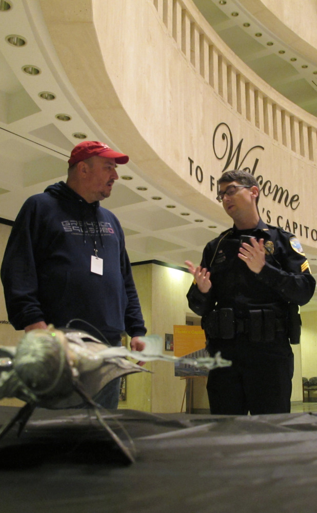 John Porgal, regional director of the American Atheists, talks with a police officer in Tallahassee, Fla.