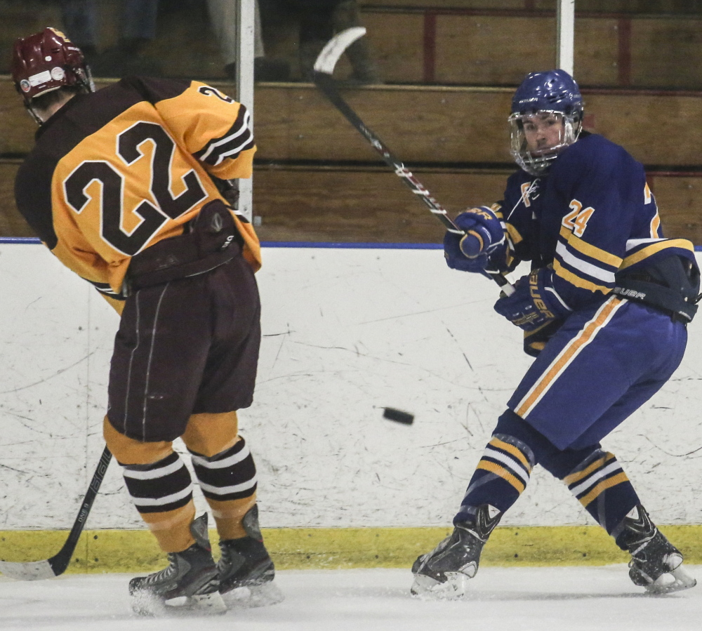 PORTLAND, ME - DECEMBER 23: Falmouth player Jake Grade hits the puck toward Cape Elizabeth's goal while Cape Elizabeth player Jack Drinan defends at the Portland Ice Arena in Portland, ME on Tuesday, December 23, 2014. (Photo by Whitney Hayward/Staff Photographer)