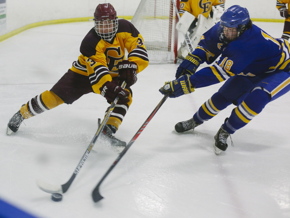 Peyton Weatherbie of Cape Elizabeth, left, attempts to slip the puck past Isaac Nordstrom of Falmouth during their schoolboy hockey game Tuesday night at the Portland Ice Arena. Falmouth remained unbeaten with a 3-2 victory.