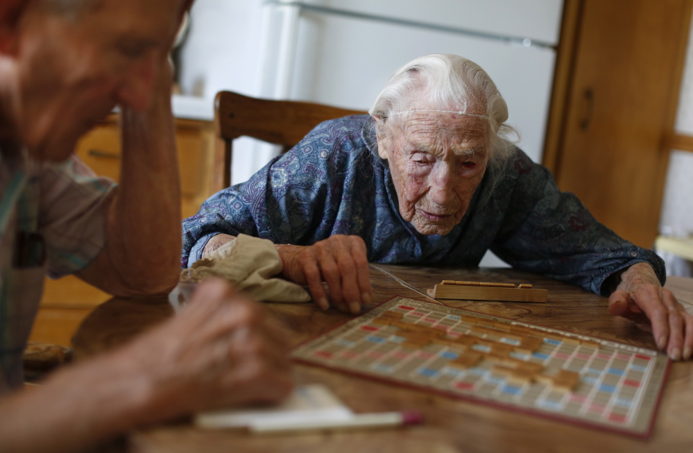 Anna Stoehr plays Scrabble at her home in Pottsdam, Minn., with her son, Harlan. Stoehr had recently joined Facebook, which sent her a bouquet of 114 flowers on her birthday.