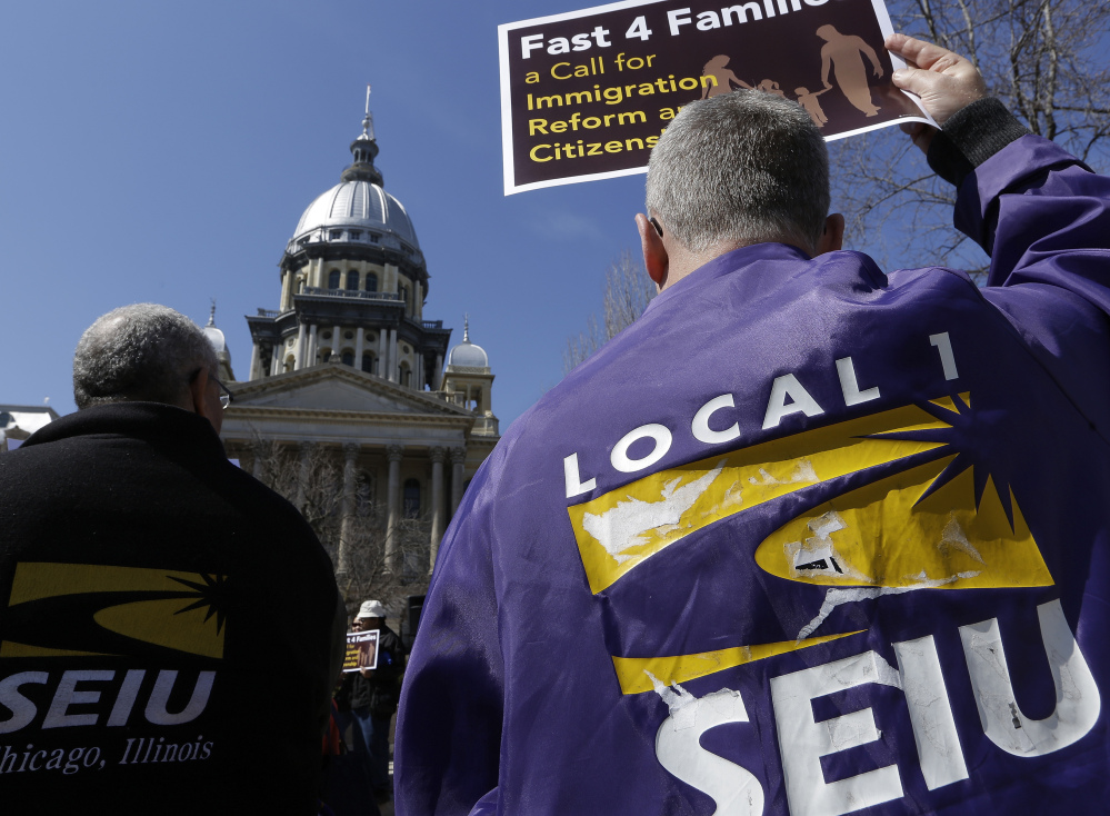 Members of the Service Employees International Union rally in March in front of the Illinois State Capitol in support of immigration reform. Unions across the country are reaching out to immigrants affected by President Obama's recent executive action in hopes of expanding their dwindling ranks by recruiting millions of workers who entered the U.S. illegally.