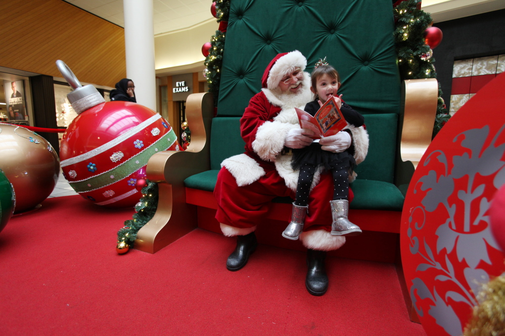 Good time management allows Santa to read to 4-year-old Paige Brooks at the Maine Mall even as the big day approaches in 2014.