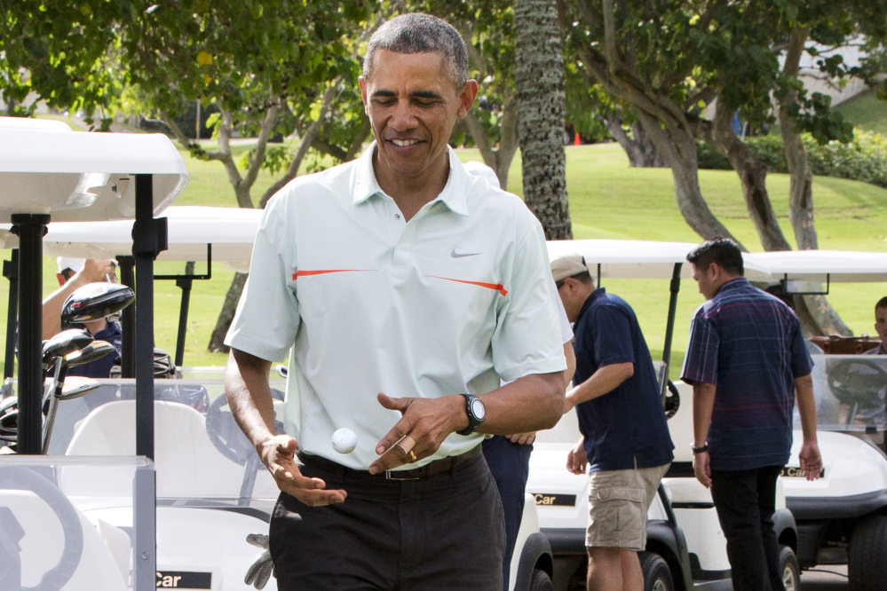 Surrounded by Secret Service Agents, President Barack Obama  tosses a golf ball between his hands after finishing the 18th hole of a game of golf with Malaysian Prime Minister Najib Razak on Wednesday at Marine Corps Base Hawaii's Kaneohe Klipper Golf Course in Kaneohe, Hawaii, during the Obama family vacation.
