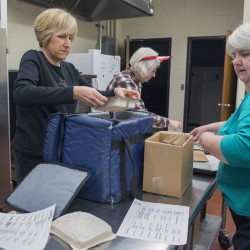 WEST BROOK,  ME - DECEMBER 25: Staff from the Southern Maine Agency on Aging and volunteers from the Portland Rotary Club delivered hot meals to homebound seniors who would be alone for Christmas Day. Volunteers Jackie Harkins (left), Deb Welton, and Beth Miller (right) load insulated bags with hot meals for delivery to area seniors. (Photo by (John Ewing/Staff Photographer)