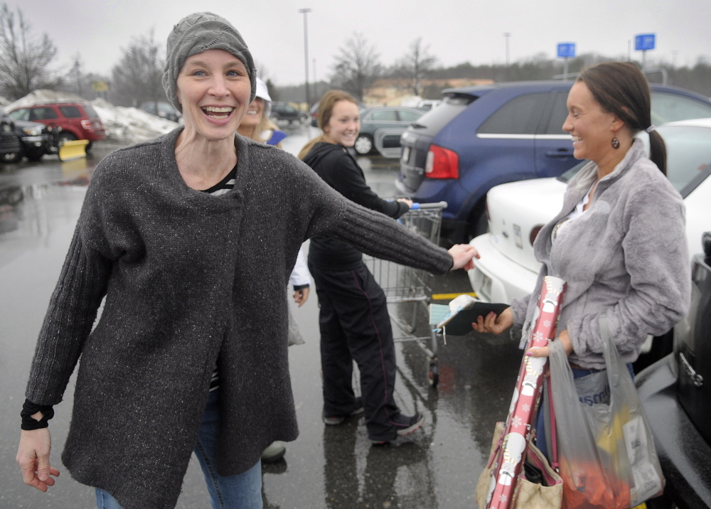 "Karyn Sweeney, left, hands Sierra Warner of Monmouth a gift Wednesday in the parking lot of Wal-Mart in Augusta. ""This is probably the best Christmas I've ever had in my life,"" Sweeney said. ""There are lots of free hugs."""