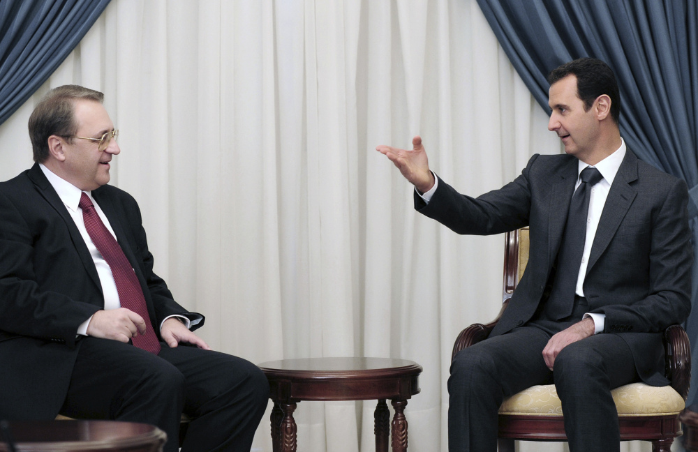 Syrian President Bashar Assad, right, speaks with Russia's Deputy Foreign Minister Mikhail Bogdanov on Dec. 10 in Damascus. The search for a negotiated settlement to the Syrian civil war is gaining steam.