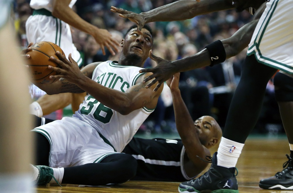 The Celtics' Marcus Smart looks to pass after winning the battle for a loose ball with Brooklyn's Jarrett Jack, bottom right, in the third quarter of Friday's afternoon game in Boston. The Nets won, 109-107, as Jack scored 27 points.