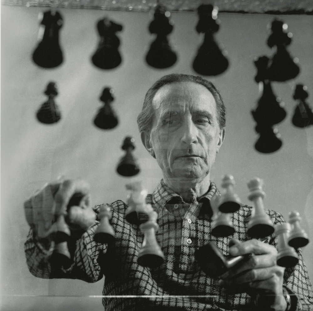 Portrait of Duchamp playing chess at his 14th Street Studio in New York in 1958. Gelatin silver print by Arnold T. Rosenberg.