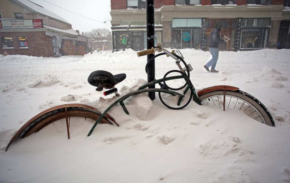 A mid-December snowstorm buried this bicycle on Congress Street in Portland last winter.
