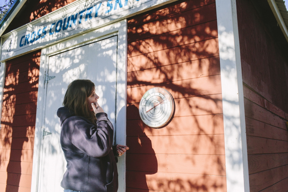 "Hillary Knight looks at a temperature gauge at Smiling Hill Farm in Westbrook, where the cross-country ski trails were open for three days after Thanksgiving. ""Everything's ready,"" she said. ""We're just waiting for snow."""