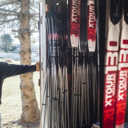 "Hillary Knight, barnyard and cross-country ski manager at Smiling Hill Farm in Westbrook, looks at the rental skis Friday. ""It would be nice to have some snow on the ground, some people here and some income coming in,"" she said."