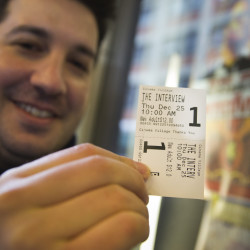 "Derek Karpel holds his ticket to a screening of ""The Interview"" at Cinema Village movie theater in New York on Thursday. The film raked in just over $1 million in ticket sales."