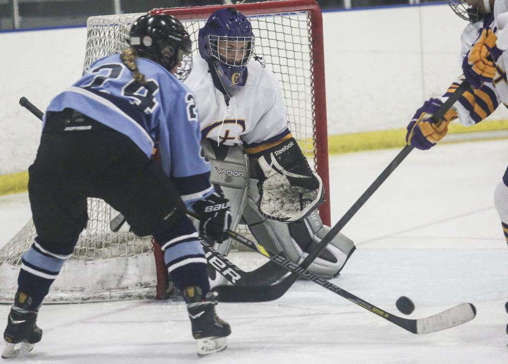 Cheverus goalie Taylor Courtois, who finished with 25 saves, sets up to stop a scoring bid by Katherine Bertolini of York during York's 4-3 victory Friday at the Portland Ice Arena.