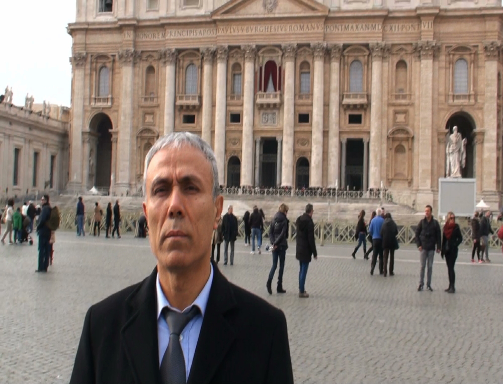 "Mehmet Ali Agca stands in front of St. Peter's Basilica at the Vatican, on Saturday. The Turkish gunman who shot and wounded John Paul II in 1981 and who has been pardoned by the pontiff was heard to mumble, ""A thousand thanks, saint."""
