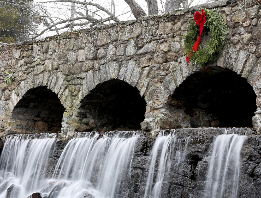 A wreath hangs above a waterfall at Case Pond in Manchester, Conn. It is a mystery who adds the wreath to the bridge every December, but the holiday flair is welcome.