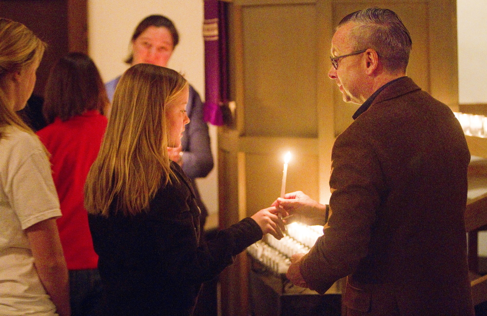 Lucy Hartley of South Portland takes a candle from usher Philip Hamilton at St. Alban's Episcopal Church in Cape Elizabeth during a Celtic Eventide service on Dec. 7. The church's pastor hopes to attract faithful Christians as well as fallen-away believers and those who've never attended church.