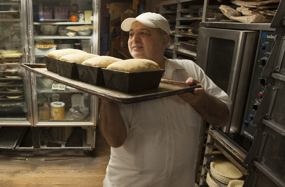 Daryl Buck removes bread from an oven at Hillman's Bakery in Fairfield on Tuesday morning.