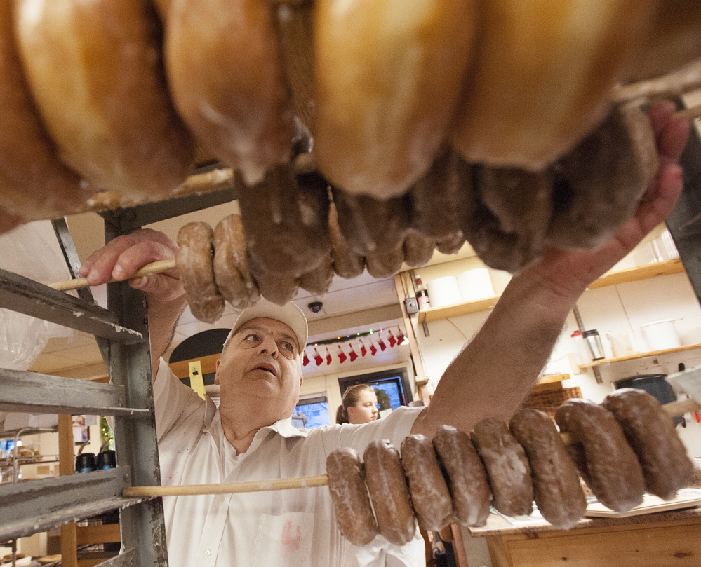 """Daryl Buck, 66, removes glazed doughnuts from a rack at Hillman's Bakery in Fairfield on Tuesday morning. """"Since I was 12 years old, this has been a big part of my identity,"""" he said."""
