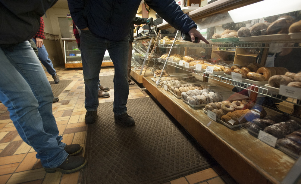 Customers point out the doughnuts they want at Hillman's Bakery in Fairfield on Tuesday morning. Daryl Buck has baked the doughnuts and pastries at Hillman's on and off since he was 13. Wednesday was Buck's last day making doughnuts and pastries at Hillman's.