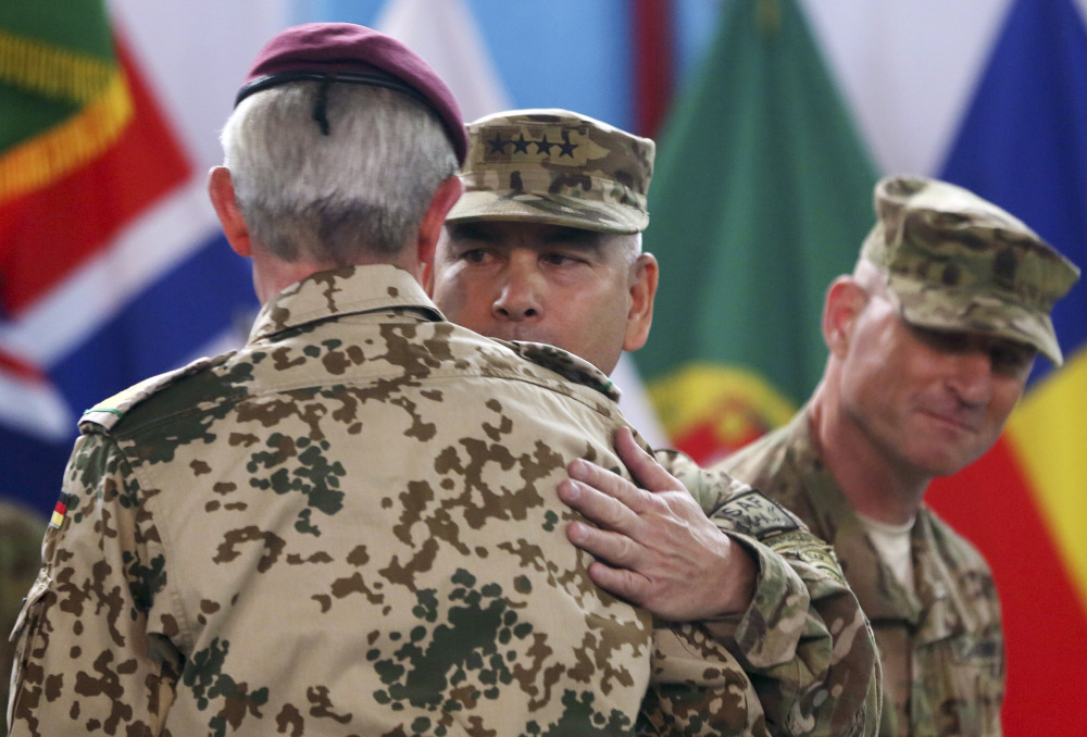 Commander of the International Security Assistance Force, Gen. John Campbell, center, hugs ISAF Gen. Hans-Lothar Domrose, as Command Sgt. Maj. Delbert Byers watches them during a ceremony at the ISAF headquarters in Kabul, Afghanistan, on Sunday.