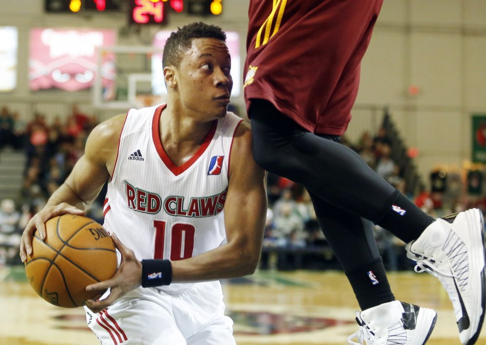 Maine's Tim Frazier tries to find someone to pass to with a Canton Charge defender high above him. Frazier scored 15 points on Sunday, but the Red Claws suffered their first loss at home this season, 99-98.