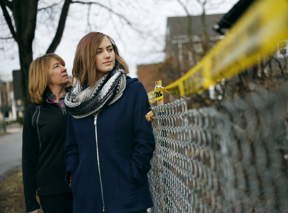 "Catherine Wilson, left, and Grace Damon look over police barrier tape at the burned building at 20-24 Noyes St. in Portland. Damon, 23, who knew two of the fire victims, said that trying to form a tenant union to defend renters' rights is ""I guess my way of grieving."""
